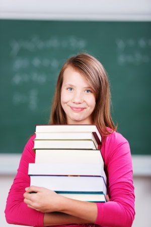 Portrait of a smiling young schoolgirl wearing a pink sweater holding a pile of thick books in the classroom with the chalkboard in the background photo
