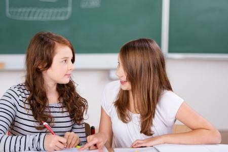 2 陽気な学生の学校のお部屋にノートを書いている間話しています。 写真素材 - 20736097