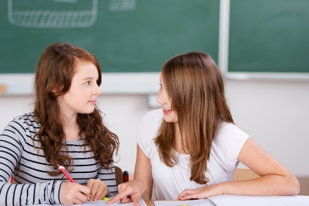 Two cheerful students talking while writing notes in school room
