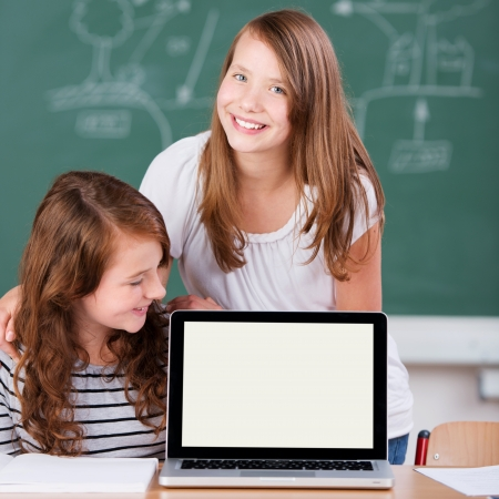 Two Elementary students studying with computer inside the school photo