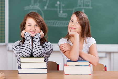 early education: Young cheerful students sitting with stack of books in front of blackboard Stock Photo