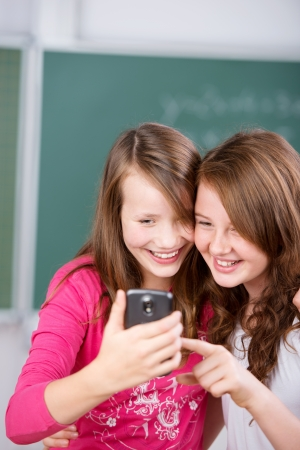 Two happy students holding cellular phone inside the school classroom photo