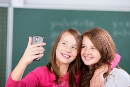 Two elementary students taking a picture of themselves inside the room photo
