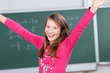 sumas: Retrato de estudiante feliz levantando las manos delante de la pizarra