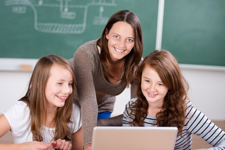 Female teacher teaching her two students with laptop inside the classroom photo