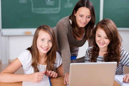 computer lesson: Cheerful teacher teaching her two students with laptop inside the classroom