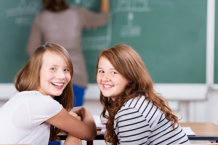 inattentive: Young cheerful students during the class in schoolroom