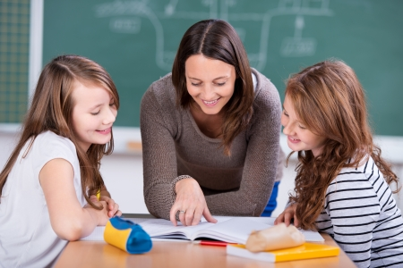 teacher student: Happy teacher teaching her two students inside the school Stock Photo