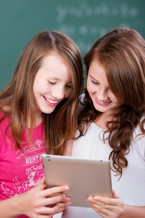Two cheerful female studying with digital laptop in a close up shot photo