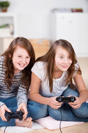 niños jugando videojuegos: Dos chicas jóvenes jugando alegremente videojuegos en una consola que se sienta en el suelo de la sala