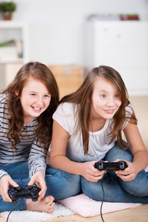 Two young girls happily playing video games in a console sitting on the living-room floor photo