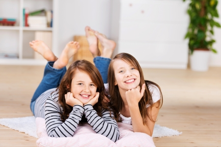 Two happy young teenage girls smiling to camera while laying on the bedroom floor over pillows photo