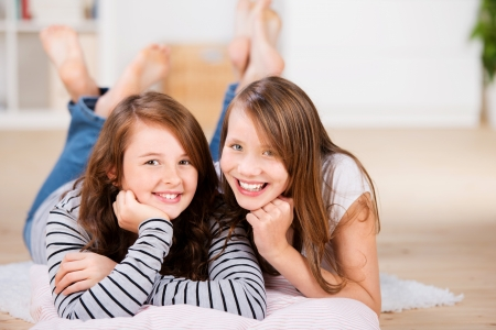 Two happy young best friend teenage girls, smile to the camera, while laying on the bedroom floor over pillows Stock Photo