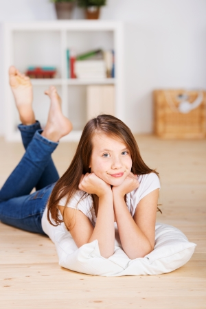Close-up portrait of an annoyed young teenage girl laying on the floor of her bedroom on her stomach over a pillow with bare-feet raised and crossed Stock Photo - 20736088