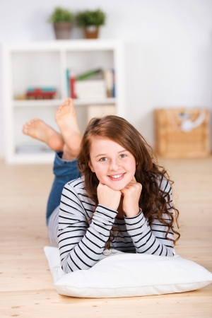 Close-up portrait of a smiling young teenage girl laying on the floor of her home on her stomach over a pillow with bare-feet raised and crossed photo