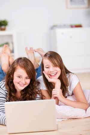 Close-up of two amused and smiling young teenage girls laying on the bedroom floor over pillows while using a laptop photo
