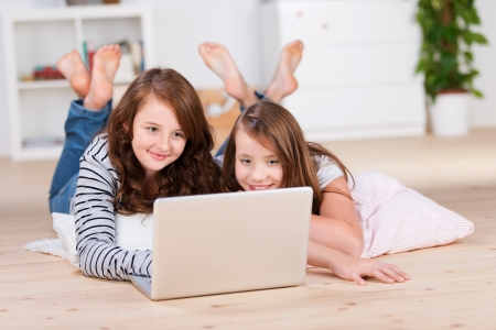 Two amused young teenage girls laying on the bedroom floor over pillows while using a laptop photo