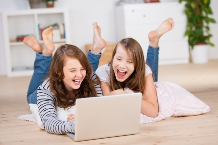 Two young teenage girls laying on the bedroom floor over pillows and using a laptop, laughing out loud photo