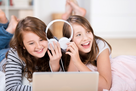 sleepover: Close-up of two happy young teenage girls sharing headphones connected to a laptop to listen to music while laying on the living-room floor