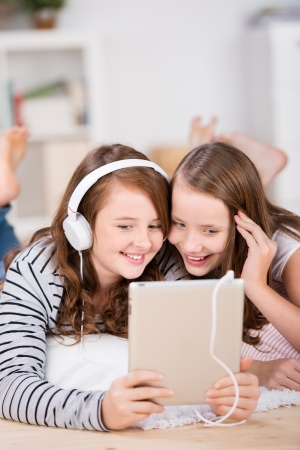 Close-up of two happy young teenage girls sharing headphones connected to a tablet to listen to music while laying on the living-room floor photo