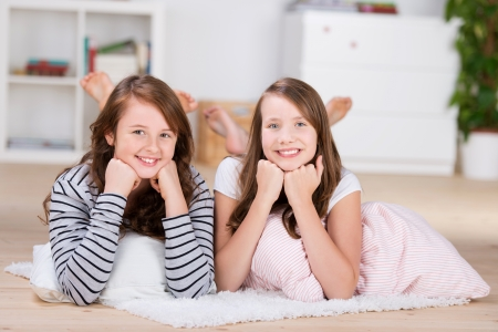 slumber party: Two pretty young teenage girls smiling to camera while laying on a house floor over pillows