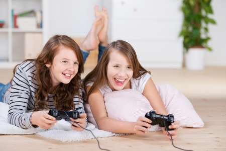 Two young girls happily playing video games in a console laying on the living-room floor
