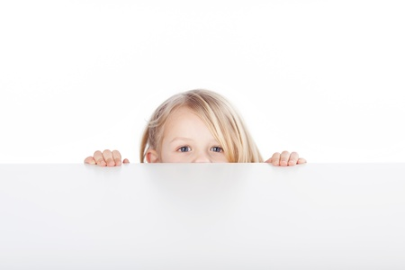 peeking: Portrait of little blond girl peeking over table isolated over white background Stock Photo