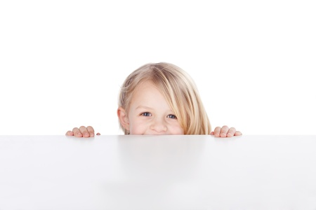 peeking: Portrait of happy little girl peeking over table isolated over white background Stock Photo