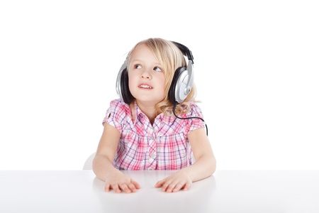 Pretty little blond girl wearing a set of headphones which are too large for her staring up into the air as she listens to the music enjoying her leisure time photo