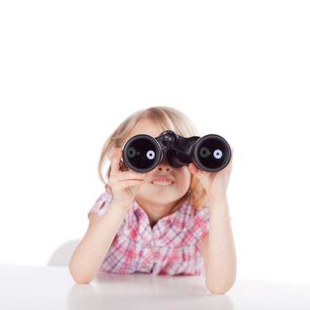 Little girl sitting at a table looking through binoculars viewing something exciting in the distance, on a white background photo