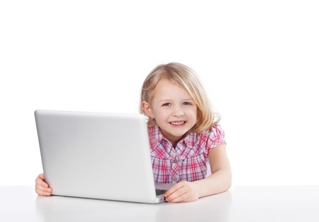 cheeky: Grinning attractive little girl sitting at a table using a laptop looking around the side at the camera with a cheeky smile Stock Photo