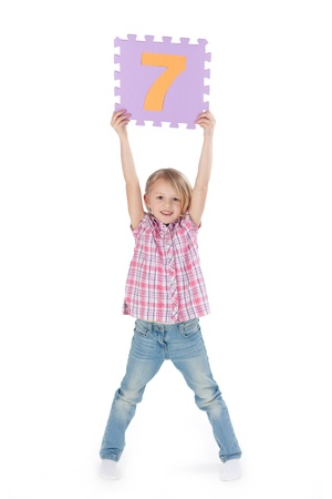 seven persons: Full length portrait of happy girl with arms raised holding number 7 puzzle piece isolated over white background