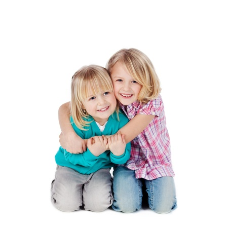 siblings: Portrait of little girl embracing sister isolated over white background