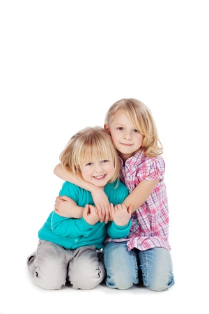 Two cute little blond sisters kneeling on the floor arm in arm cuddling each other in a loving embrace, on white photo