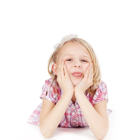 Funny little girl lying on her stomach on the floor with her chin resting on her hands smiling to herself, on a white background photo