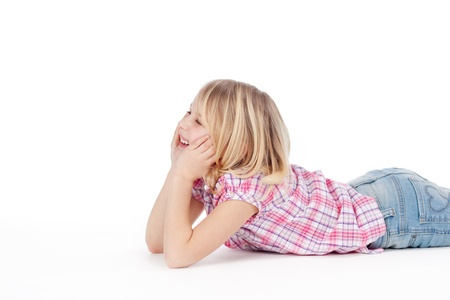 Pretty little girl lying on her stomach on the floor with her chin resting on her hands smiling to herself, on a white background Stock Photo