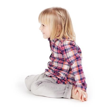 en cuclillas: Vista lateral al linda chica sentada aislados sobre fondo blanco