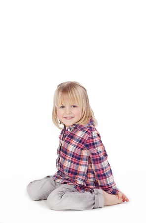 Full length portrait of cute blond little girl sitting isolated over white background photo