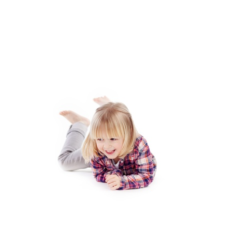 Beautiful vivacious little blond girl romping on the floor lying on her stomach kicking her bare feet in the air photo