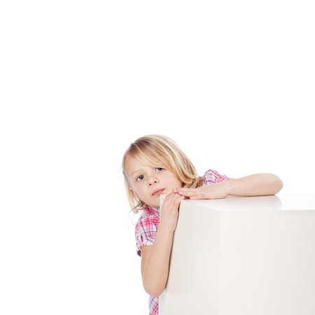 looking around: Portrait of girl hiding behind white block isolated over white background