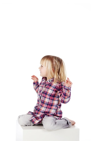 little girl barefoot: Side view at cute girl sitting on block isolated over white background