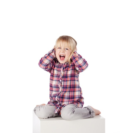 fringes: Full length portrait of cute girl shouting while sitting on block isolated over white background
