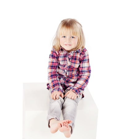 Full length portrait of cute little girl sitting on block isolated over white background