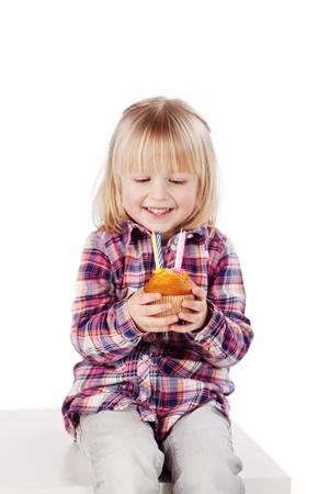 fringes: Happy cute little girl looking at candles on cupcake while sitting on block against white background
