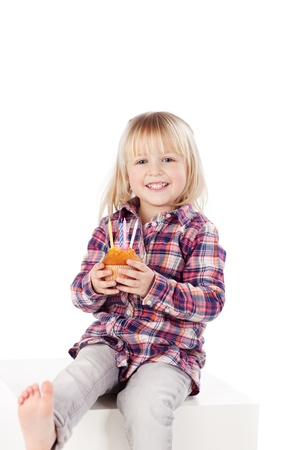 Lovable little blond girl with a birthday cake with four candles held carefully in her hand sitting barefoot on a white cabinet
