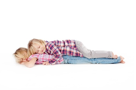 Full length of little girl lying on sister isolated over white background photo
