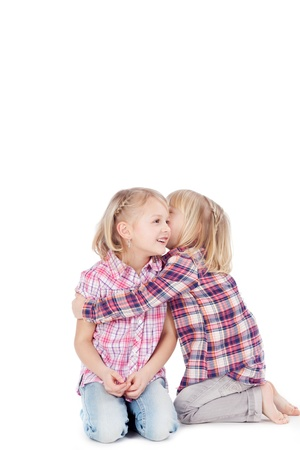 arms around: Little girl sharing secret with sister isolated over white background