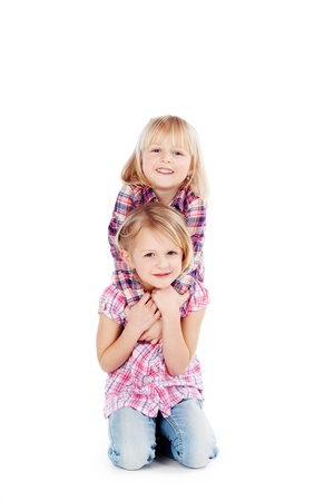 cute little girls: Ni�as lindas sonrientes junto aislados sobre fondo blanco Foto de archivo