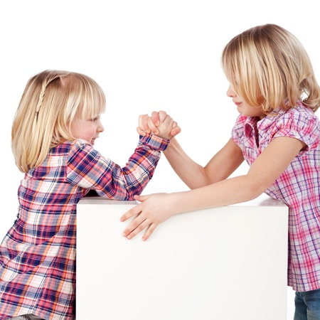 Side view of cute little girls arm wrestling isolated over white background photo