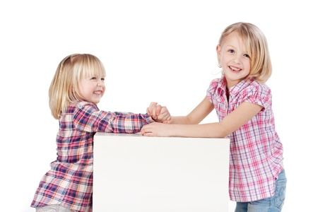 Side view of happy cute little girls arm wrestling isolated over white background photo